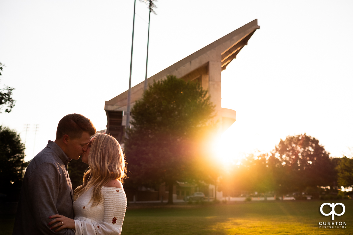Man kissing his fiancee in front of Death Valley stadium in Clemson.