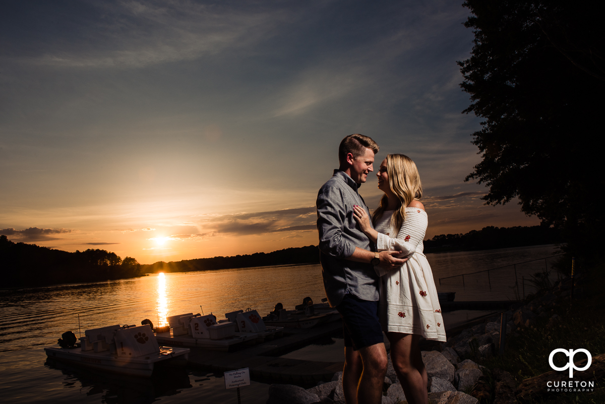 Engaged couple holding each other at sunset by the lake during a Clemson engagement session.