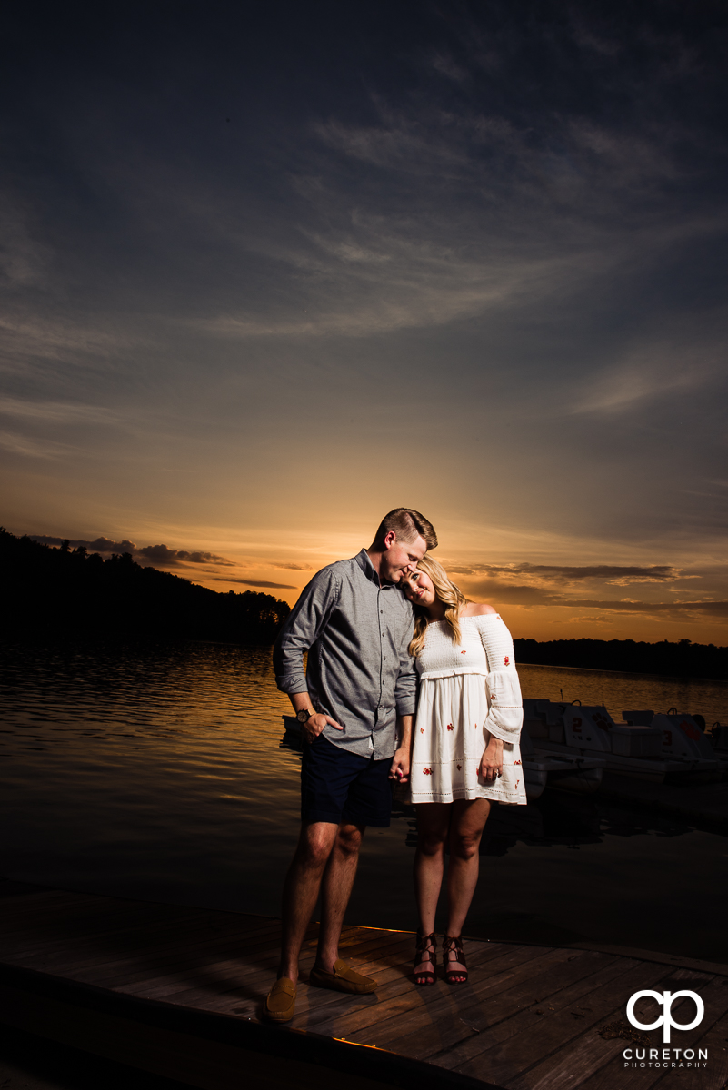 Engaged couple by the lake during an amazing Clemson sunset.