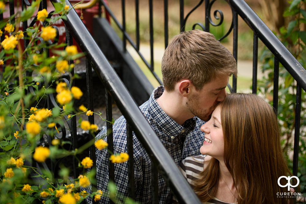 Future groom kissing his bride on the forehead during a Botanical Garden Engagement session.