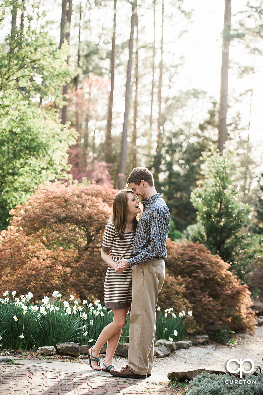 Engaged couple laughing during an engagement session at the Botanical Gardens in Clemson.