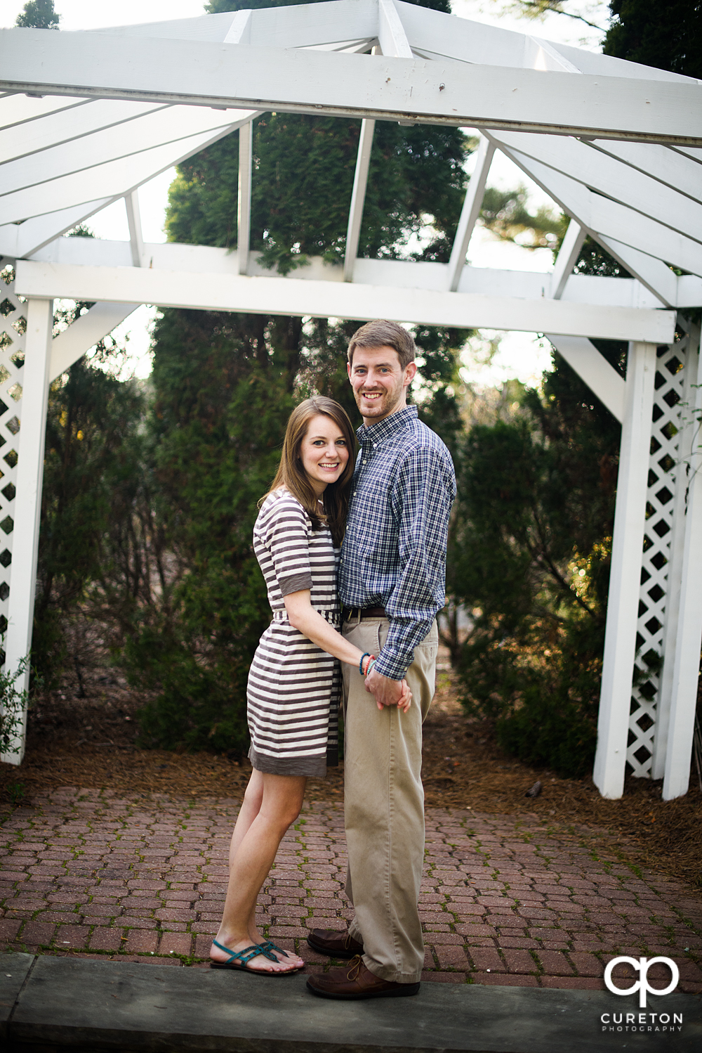 Future bride and groom smilin during an engagement session at the Botanical Gardens in Clemson.