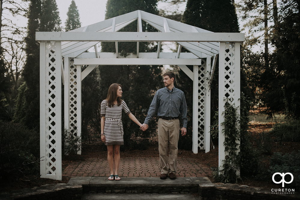 Engaged couple looking at each other during an engagement session at the Botanical Gardens in Clemson.