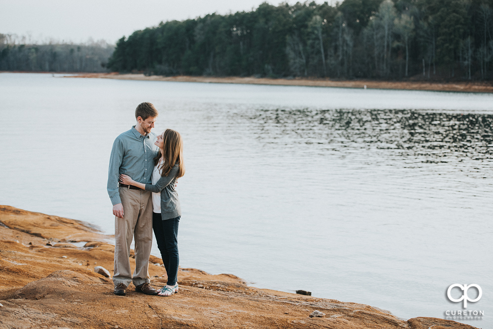 Couple walking by the lake during an engagement session at the lake in Clemson.