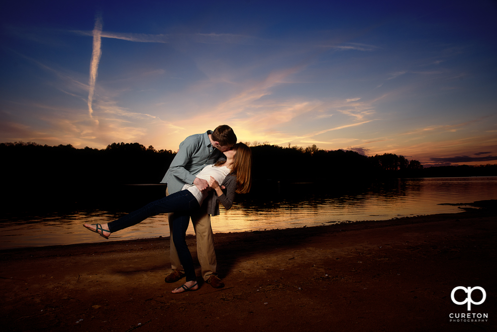 Engaged couple dipping during an engagement session at the lake in Clemson.