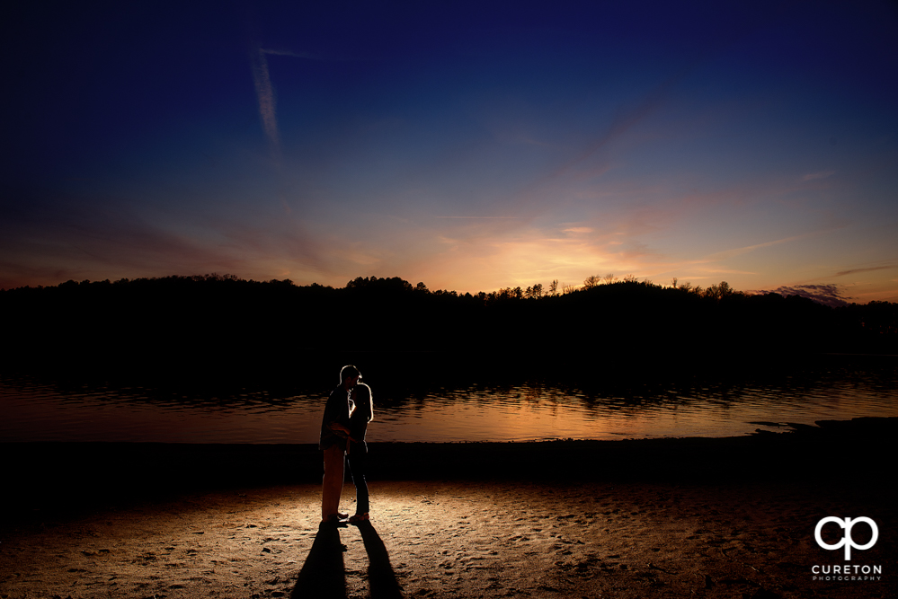 Silhouette of a couple during an engagement session at the lake in Clemson.