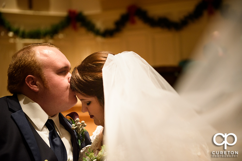Groom kissing his bride on the forehead after their Spartanburg wedding.