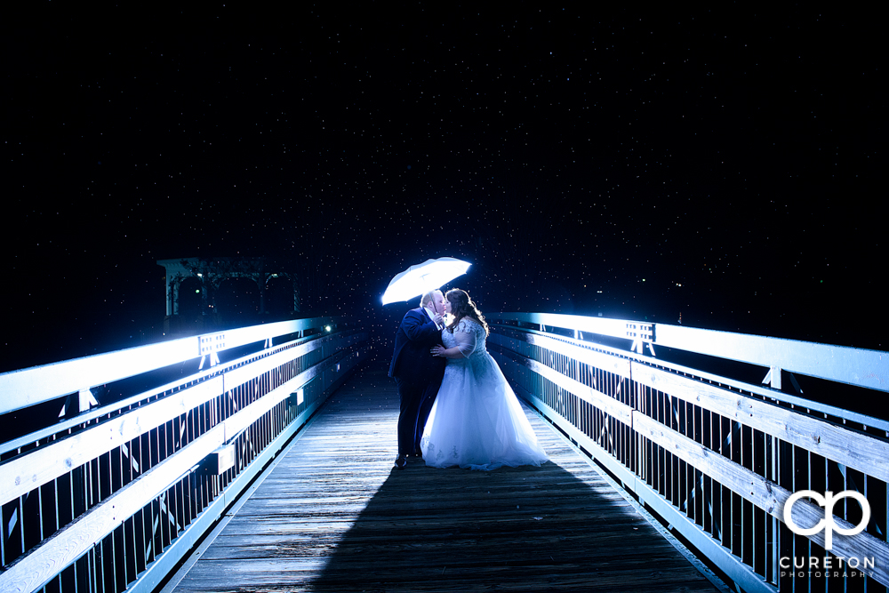 Bride and groom on a bridge in the rain during their Cleveland Park wedding reception.