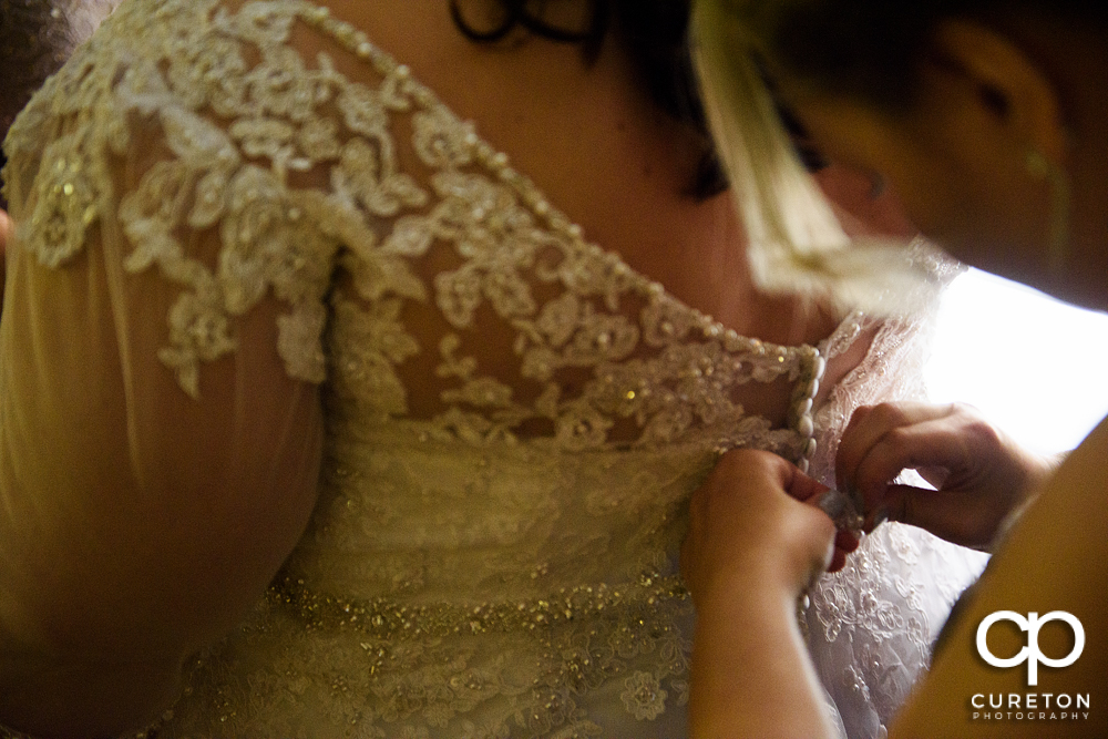Bride getting the back of her dress buttoned.