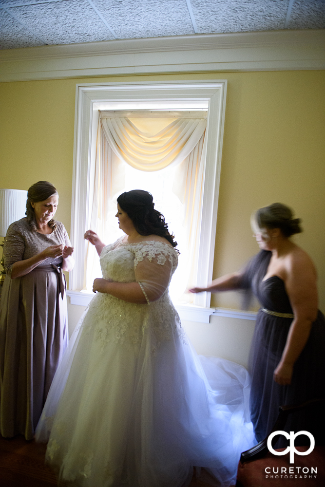 Bridesmaids helping the bride get into the dress.