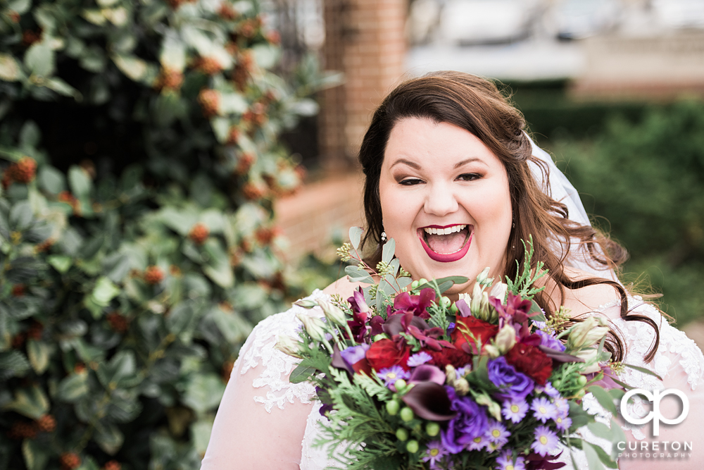 Bride smiling with her flowers.