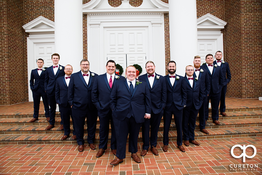 Groom and groomsmen on the steps of the church.