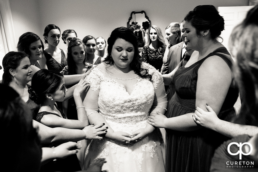 Bridal party praying with the bride before the ceremony.