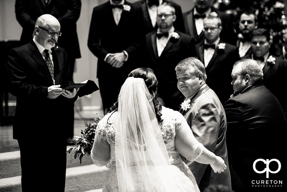 Father gives away his daughter during the ceremony.