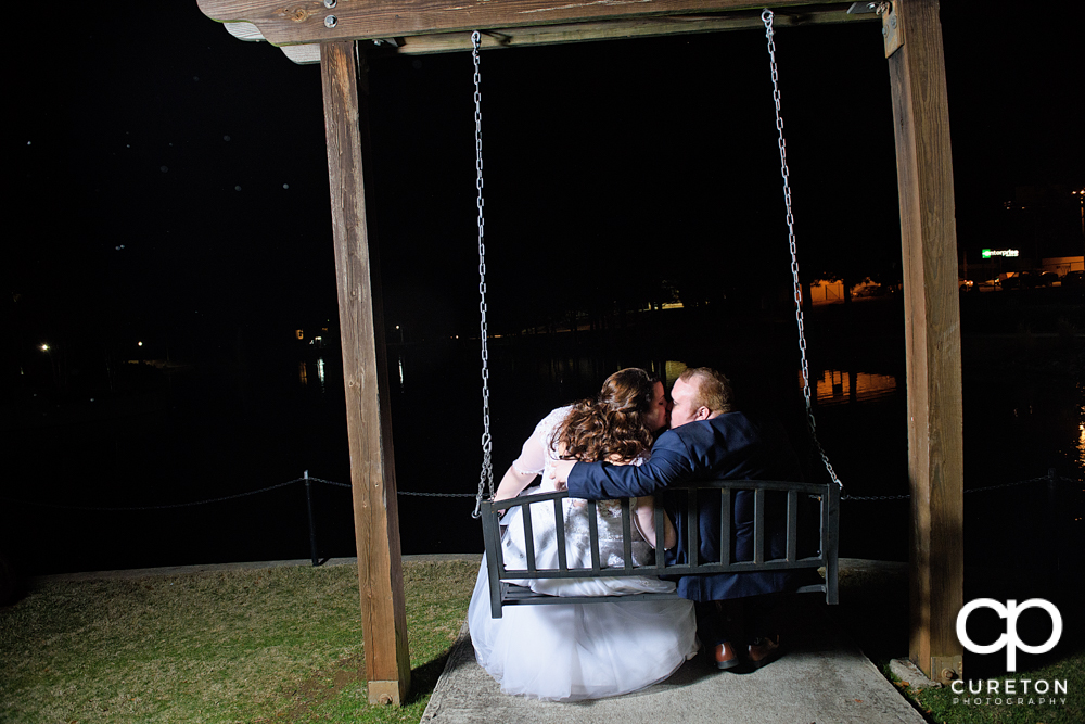 Bride and groom kissing on a park bench at Cleveland Park during the Spartanburg wedding reception.
