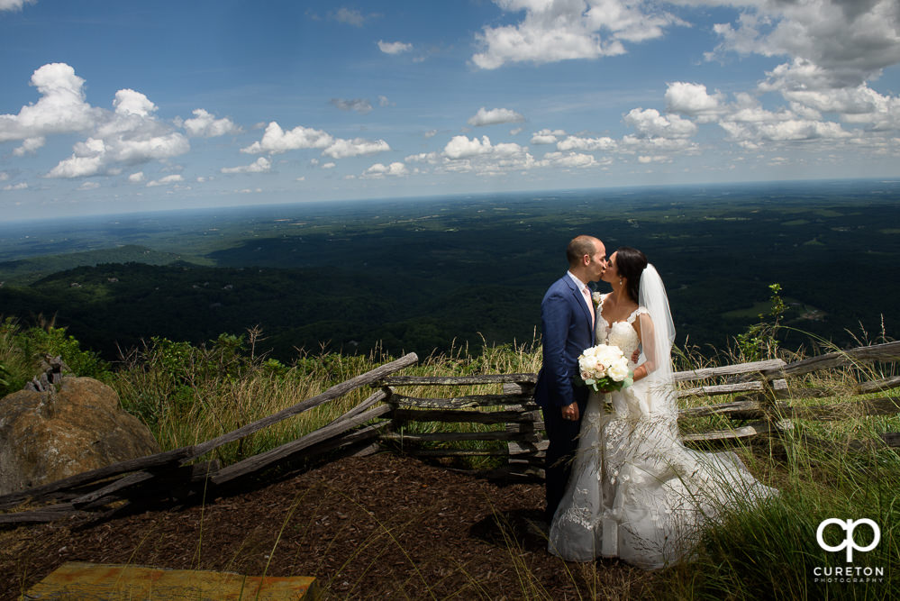 Newlyweds kissing on a cliff after their Glassy Chapel wedding.