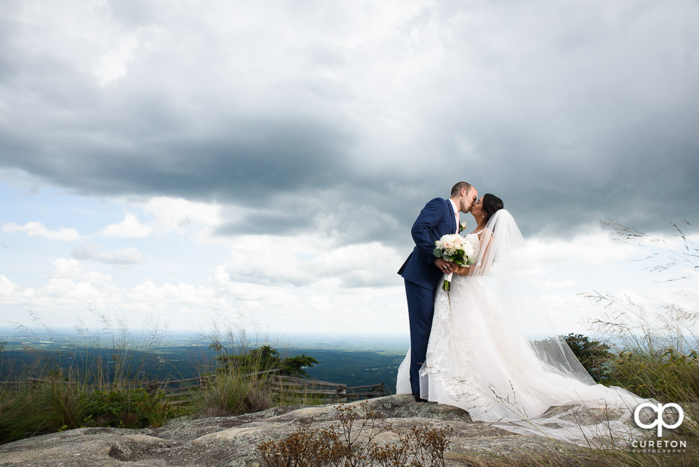 Bride and groom on top of the rock at Glassy Chapel.