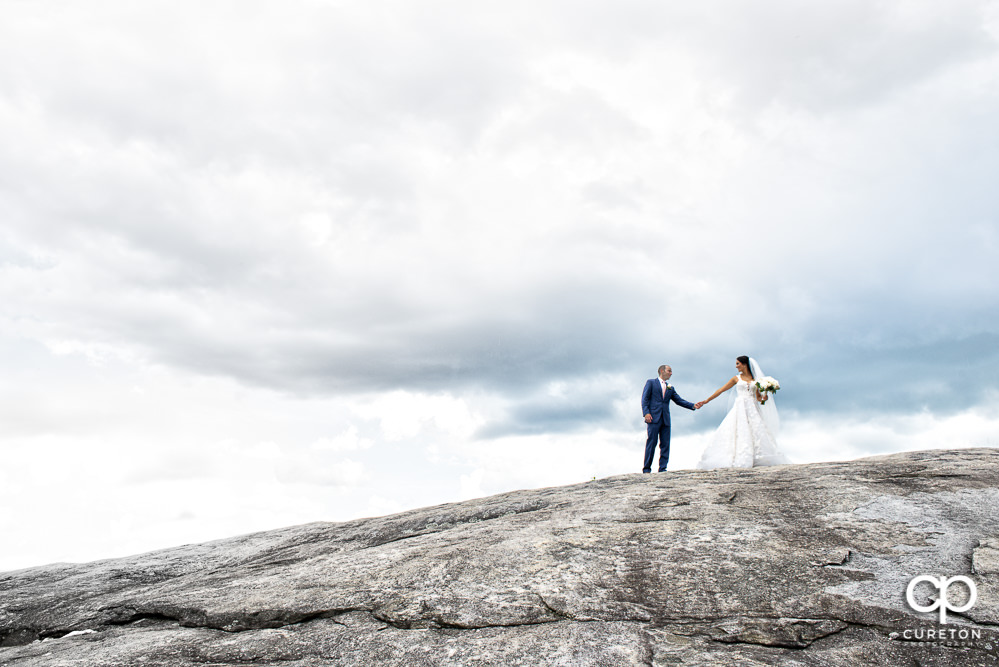 Bride and groom holding hands walking up a mountaintop after their Glassy Chapel wedding.
