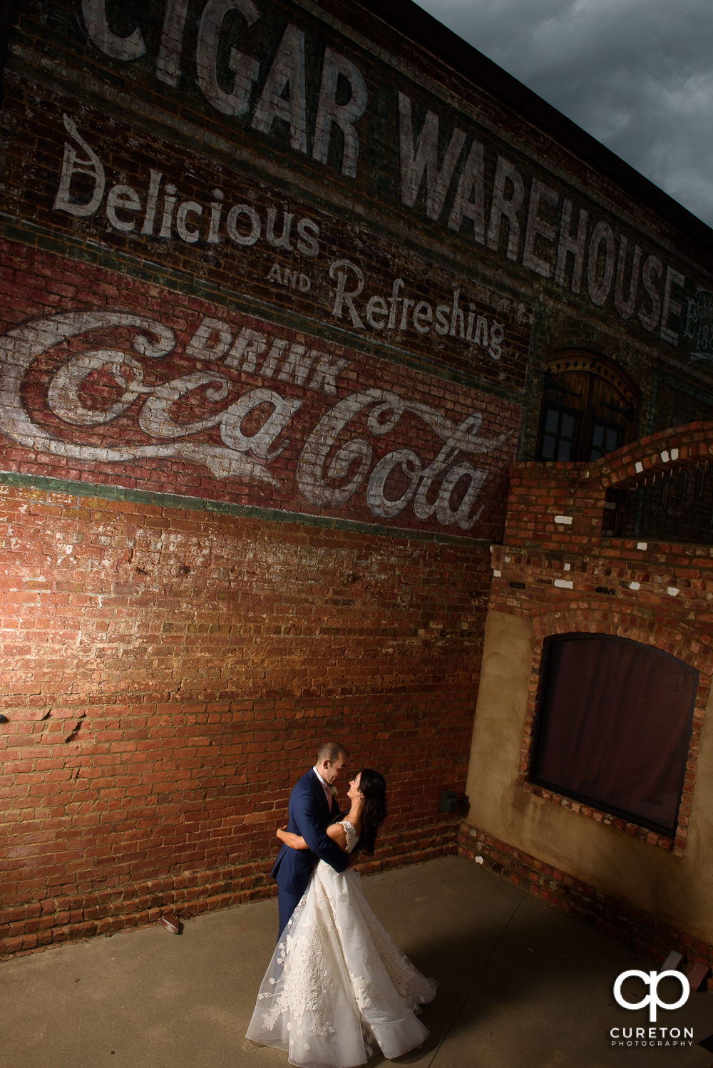 Epic photo of a bride and groom dancing under the sign at Old Cigar Warehouse.
