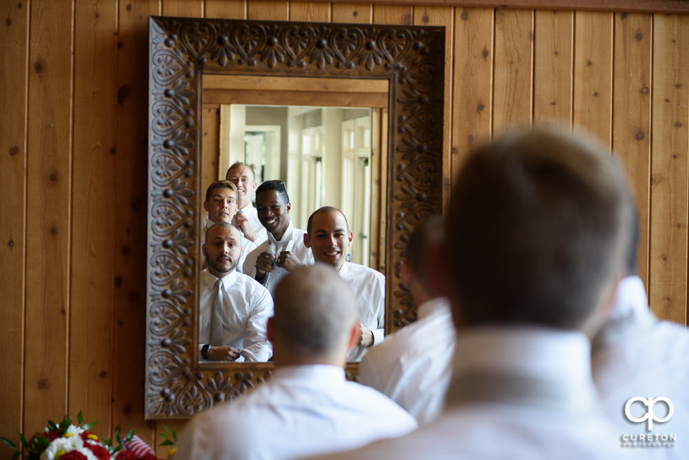 All of the groomsmen sharing a mirror getting ready.