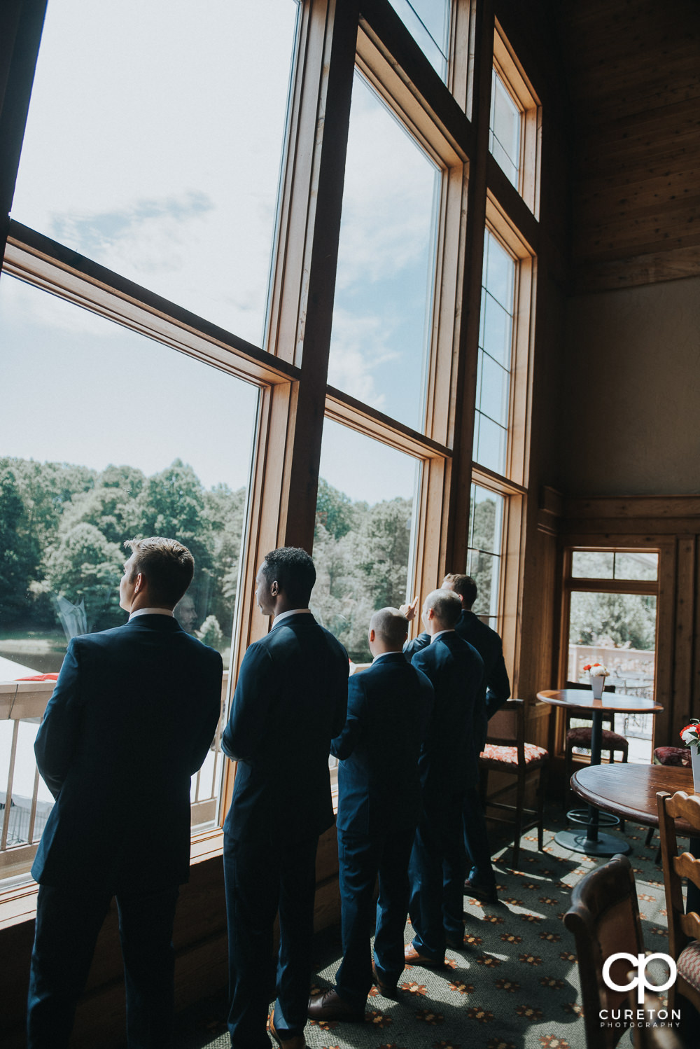 Groomsmen staring out of the window before the ceremony.
