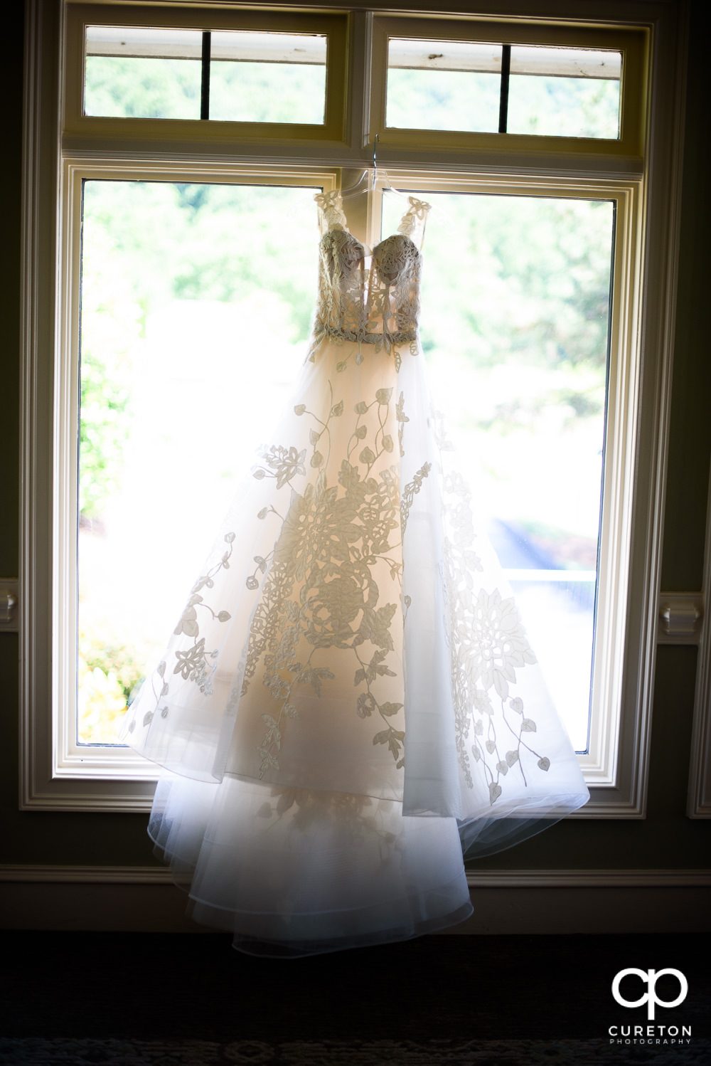 Bride's dress hanging in the window.