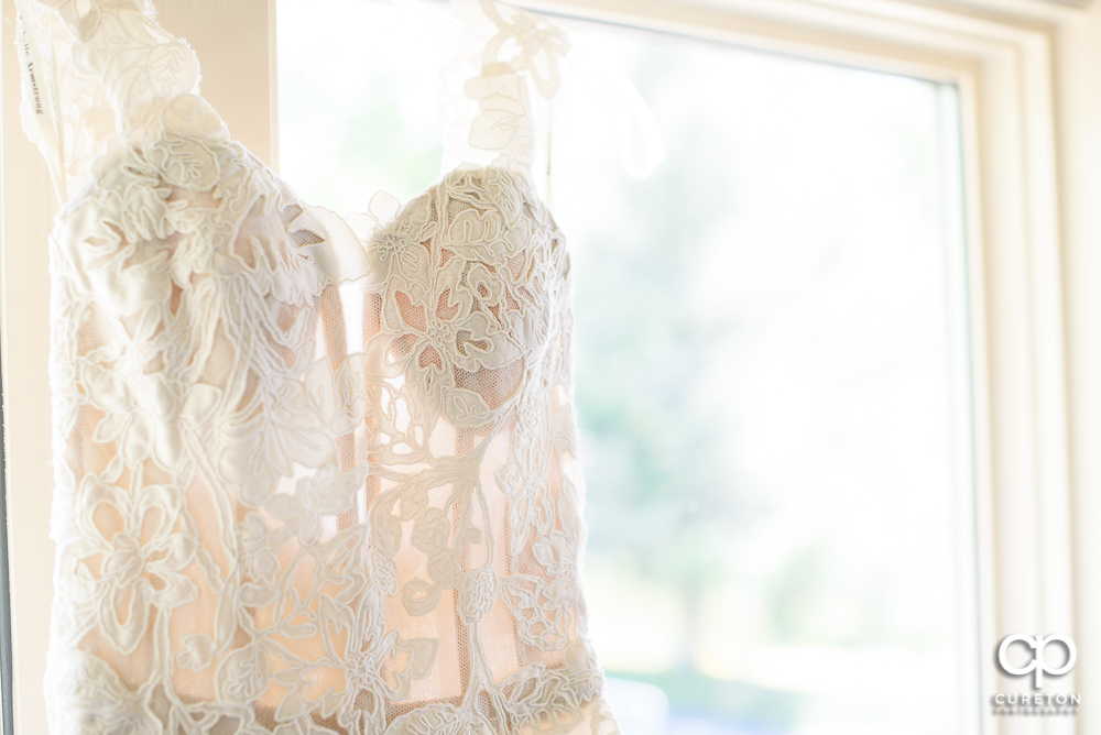 Wedding dress hanging in a window close-up.