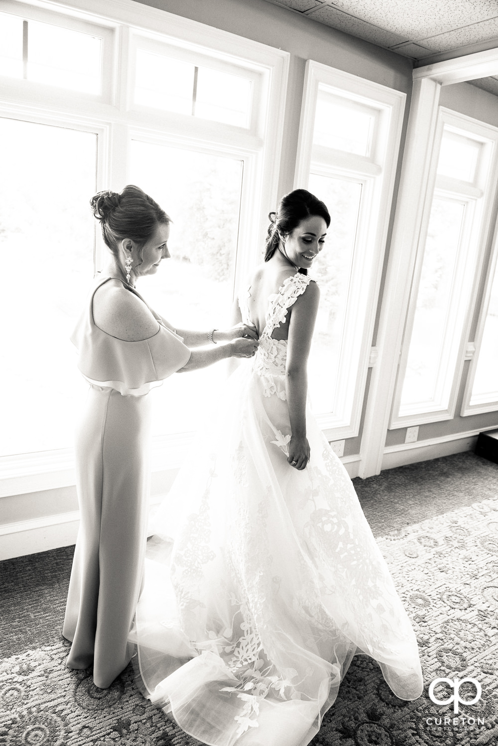 Bride's mom helping her into her wedding dress.