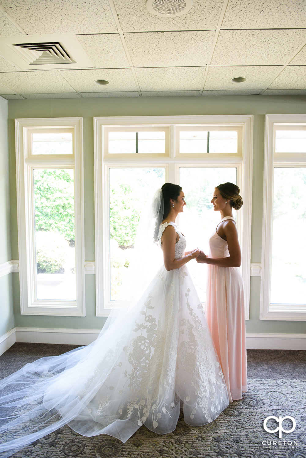 Bride and her sister holding hands.