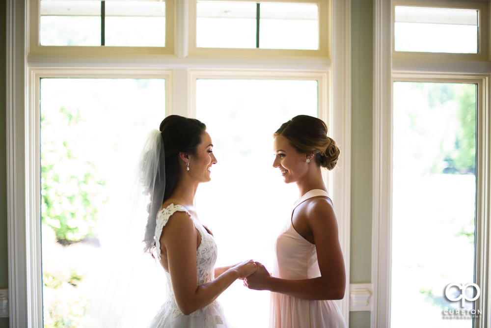 Bride and her sister laughing before the ceremony.