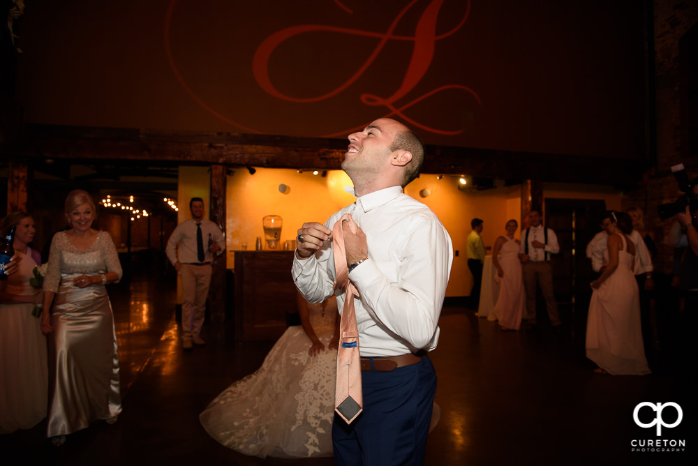 Groom taking off the garter.