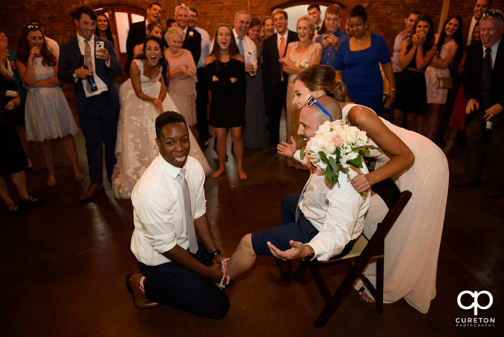 Groomsmen tricked into putting the garter on to another groomsmen instead of the woman who caught the bouquet.