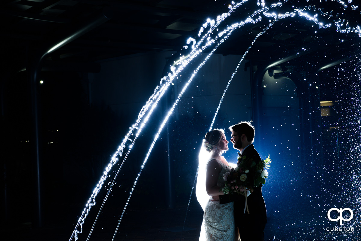Bride and groom dancing in the fountain at their Greenville Commerce Club wedding.
