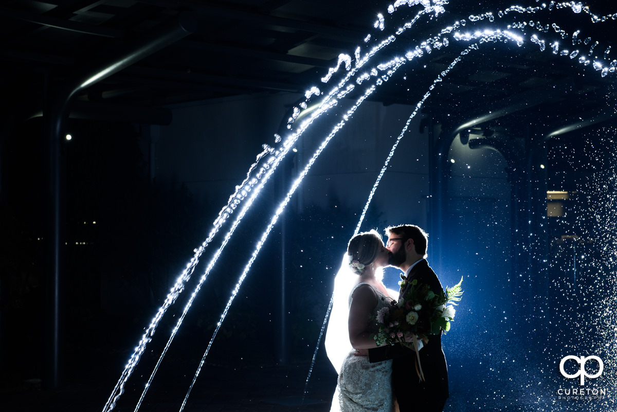Bride and groom kissing in the fountain at their Greenville Commerce Club wedding.