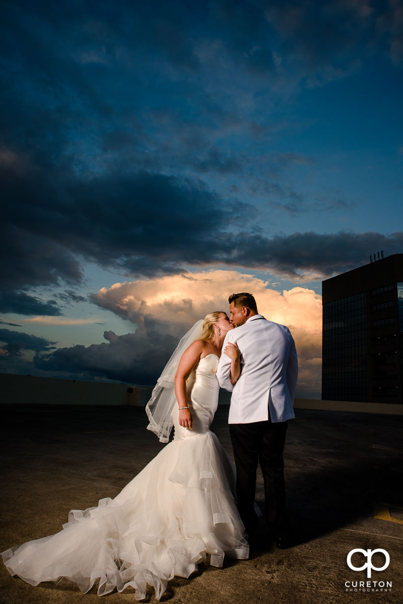 Bride and groom on a downtown Greenville rooftop at sunset during their Commerce Club wedding.