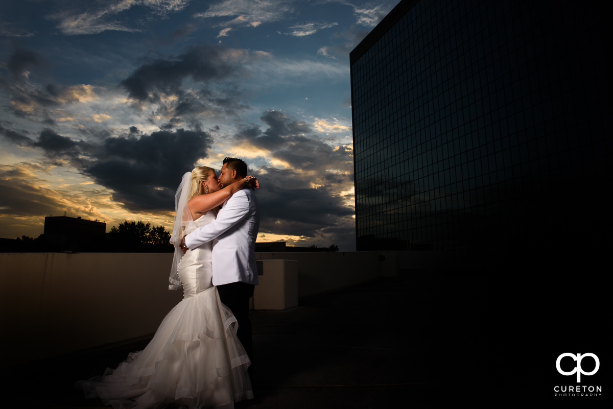 Bride and groom kissing at sunset at their Commerce Club wedding.
