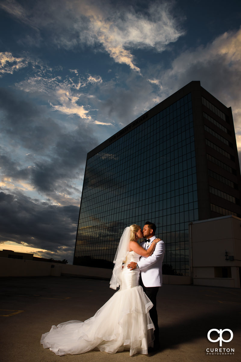 Bride and groom on top of a parking garage at sunset in downtown Greenville,SC.