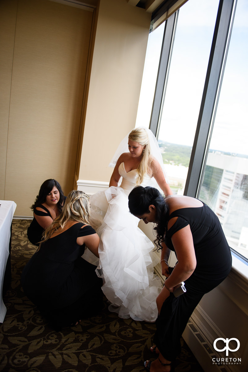 Bridesmaids helping the bride with her garter.