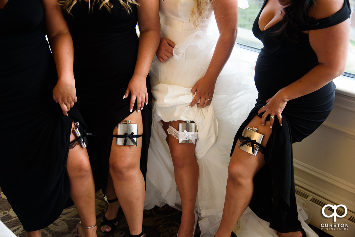 Bride and bridesmaids with flasks on their garters.