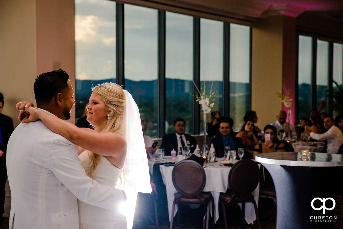 Backlit photo of bride and groom during their first dance at the Commerce Club wedding reception.