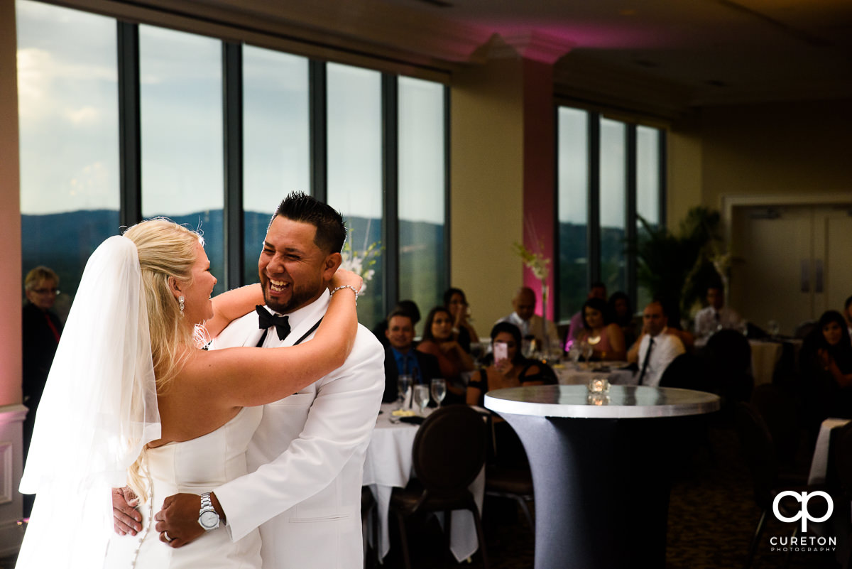 Groom laughing during their first dance at the Commerce Club wedding reception.