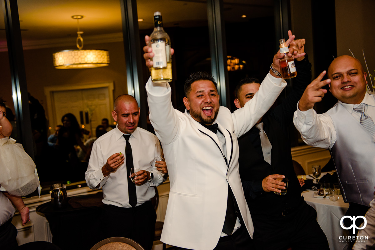 Groom holding a bottle of tequila.