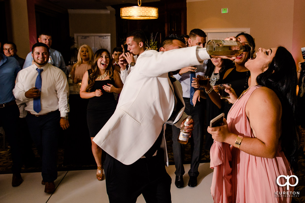 Groom pouring tequila into guests's mouths at the wedding reception.