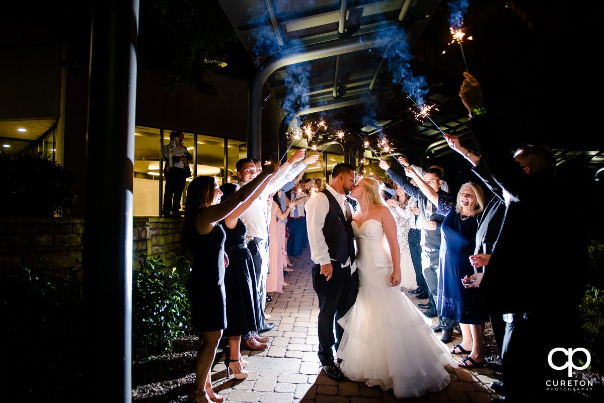 Bride and groom kissing underneath sparklers.
