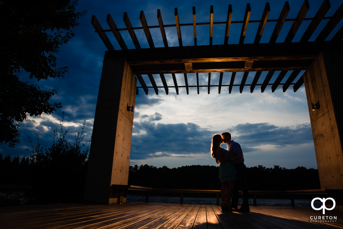 Future Bride and Groom kissing at sunset by the lake during a creative engagement session at Furman University in Greenville,SC