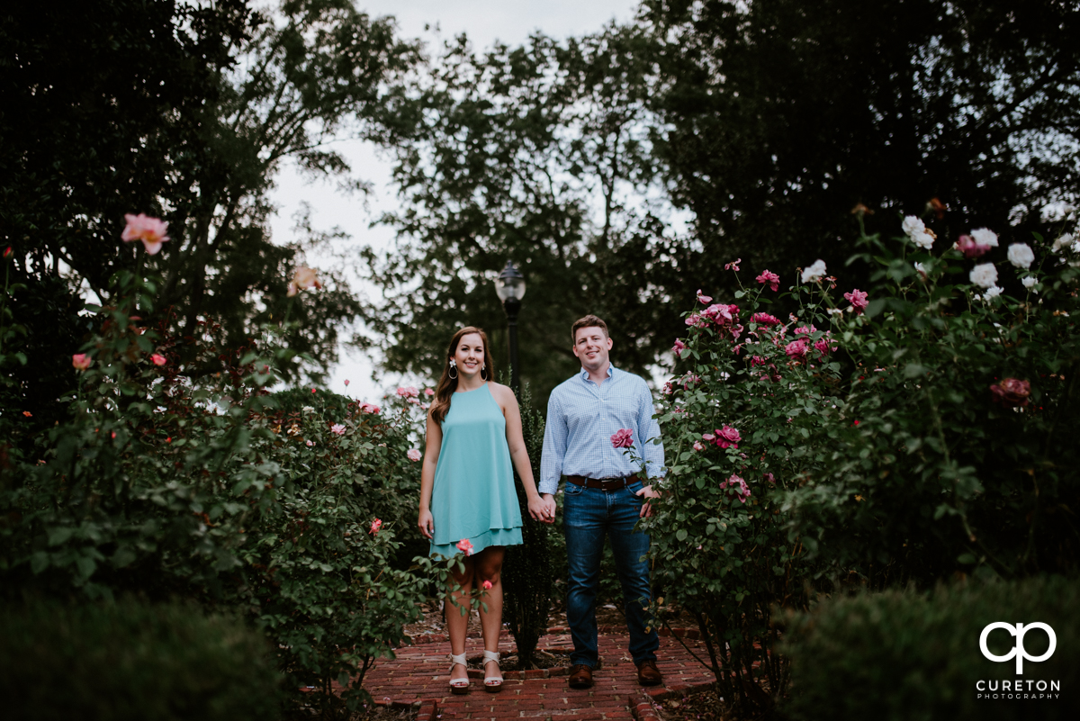 Couple holding hands in the rose garden during a creative engagement session at Furman University in Greenville,SC.