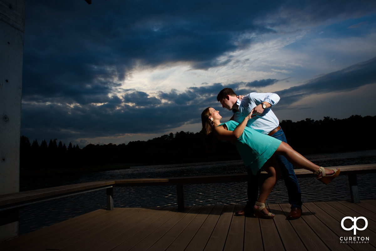 Groom dipping his future bride while dancing by the lake at sunset during a creative engagement session at Furman University in Greenville,SC.