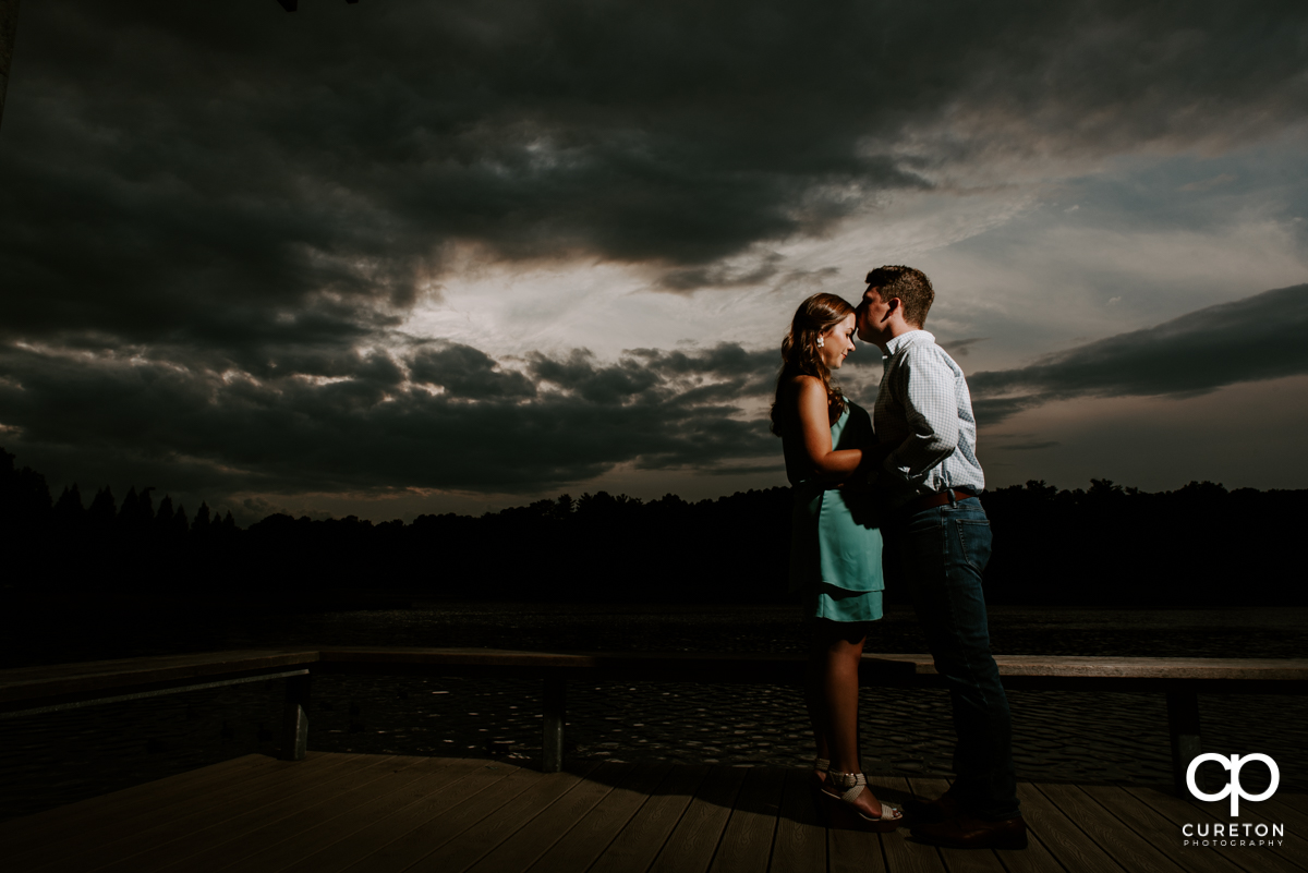 Future groom kissing his bride on the forehead at sunset by the lake during their creative engagement session.