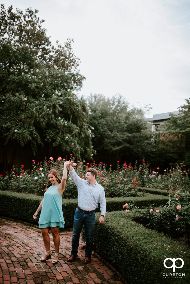 Man spinning his fiancee in the rose garden.