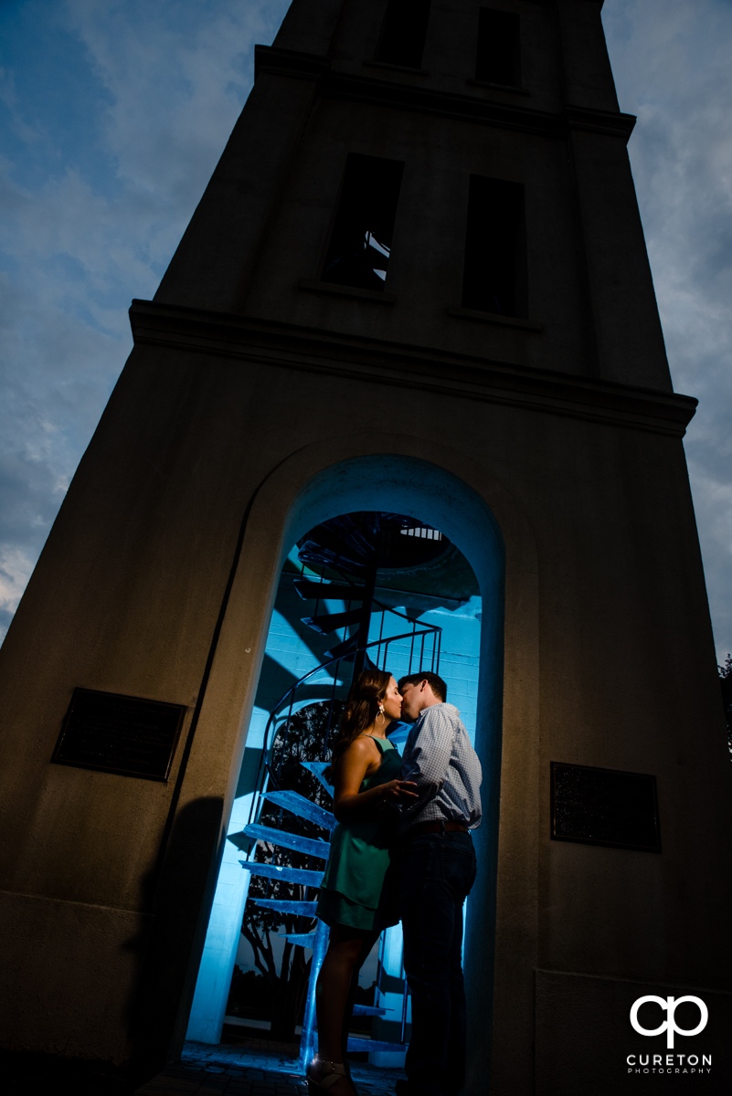 Couple kissing at the Bell Tower by the lake at Furman at their engagement session.